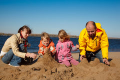El muchacho y la muchacha con los padres juegan en arena en la playa Fotografía de archivo libre de regalías