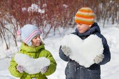 El muchacho y la muchacha del adolescente guardan corazones de la nieve Imagenes de archivo