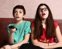 El muchacho y la muchacha del adolescente miran película con teledirigido Fotos de archivo libres de regalías