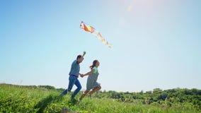 El muchacho y la muchacha del ni?o gozan el caminar con la cometa del vuelo metrajes