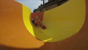 El muchacho y la muchacha divertidos ruedan con los toboganes acuáticos amarillos almacen de metraje de vídeo