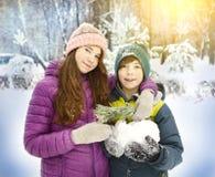 El muchacho y la muchacha en la nieve parquean el fondo Foto de archivo libre de regalías