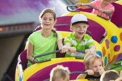 El muchacho y la muchacha en una montaña rusa que emociona montan en un parque de atracciones Imagenes de archivo