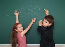 El muchacho y la muchacha escriben en consejo escolar Imagen de archivo