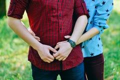 El muchacho y la muchacha están abrazando Primer de manos Imagen de archivo