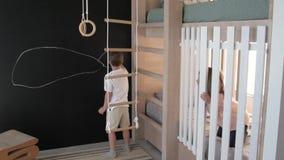 El muchacho y la muchacha están jugando en el cuarto de niños, pintando en la pared hermana con el hermano en el cuarto que juega almacen de metraje de vídeo