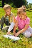 El muchacho y la muchacha están leyendo un libro Imagen de archivo
