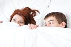 El muchacho y la muchacha están ocultando bajo la manta Imágenes de archivo libres de regalías