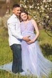 El muchacho y la muchacha felices de los pares en el flor blanco cultivan un huerto Fotos de archivo libres de regalías