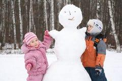 El muchacho y la muchacha hacen el muñeco de nieve Imagen de archivo