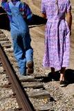 El muchacho y la muchacha jovenes caminan a lo largo de una pista de ferrocarril Foto de archivo