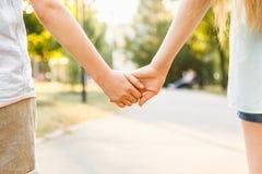 El muchacho y la muchacha jovenes llevan a cabo las manos y nos dan un paseo en el parque en soleado Foto de archivo