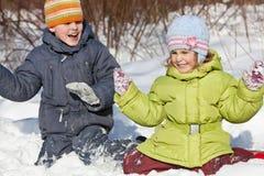 El muchacho y la muchacha juegan sentarse en nieve en invierno Imagen de archivo