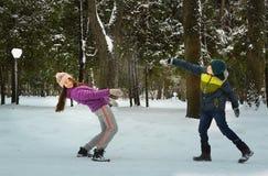 El muchacho y la muchacha lanzan bolas de la nieve en el fondo del bosque del invierno Imágenes de archivo libres de regalías