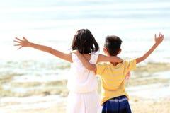 El muchacho y la muchacha levanta sus manos Fotografía de archivo