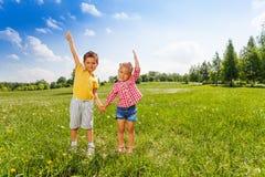 El muchacho y la muchacha llevan a cabo las manos con la segunda mano para arriba Imagen de archivo libre de regalías