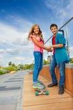 El muchacho y la muchacha llevan a cabo las manos cuando ella monta el monopatín Imágenes de archivo libres de regalías
