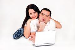 El muchacho y la muchacha miran la computadora portátil Imagen de archivo