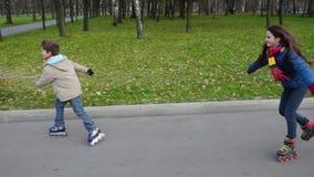 El muchacho y la muchacha montan en camino del parque del otoño en los rodillos almacen de video