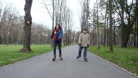 El muchacho y la muchacha montan en parque del otoño en los rodillos metrajes