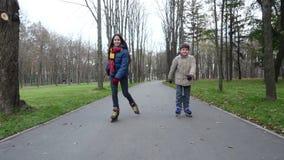 El muchacho y la muchacha montan en parque del otoño en rollerblades almacen de video
