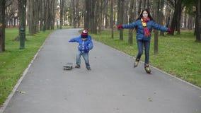 El muchacho y la muchacha montan en parque del otoño en rollerblades y scateboard metrajes