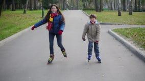 El muchacho y la muchacha montan juntos en parque del otoño en los rodillos metrajes