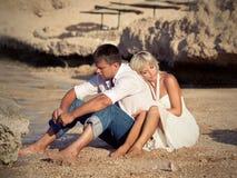 El muchacho y la muchacha piensan en la playa Fotos de archivo