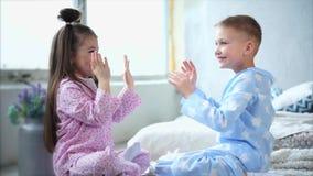 El muchacho y la muchacha preciosos vistieron en juego hecho en casa de los pijamas el juego en sus manos metrajes