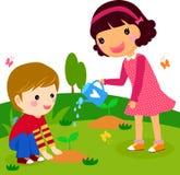 El muchacho y la muchacha riegan una planta Imagenes de archivo