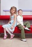 El muchacho y la muchacha se sientan de nuevo a la parte posterior Foto de archivo libre de regalías
