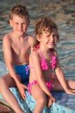 El muchacho y la muchacha se sientan en la frontera de la piscina Fotografía de archivo