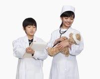 El muchacho y la muchacha se vistieron para arriba como los doctores que comprobaban las muestras vitales del oso de peluche Foto de archivo