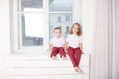 El muchacho y la muchacha son hermano y la hermana se sienta en el alféizar en la ventana fotos de archivo libres de regalías