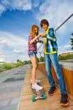 El muchacho y la muchacha sonrientes en el monopatín llevan a cabo las manos Imagen de archivo libre de regalías