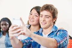 El muchacho y la muchacha toman un selfie Foto de archivo libre de regalías