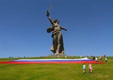 El muchacho y la muchacha van a la ayuda de los activistas que revelan una bandera rusa grande en el día de Rusia en la colina de Foto de archivo