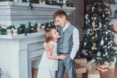El muchacho y la muchacha vistieron elegante la colocación en un cuarto brillante por la chimenea Árbol de navidad en el fondo Co imagen de archivo