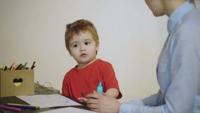 El muchacho y la mujer son de dibujo y sonrientes con los lápices coloreados aislados en un fondo blanco Psicoterapeuta que mira  almacen de video