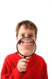 El muchacho y magnifica el vidrio Foto de archivo libre de regalías