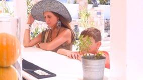 El muchacho y su madre se sientan en una barra almacen de metraje de vídeo