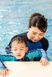 El muchacho y su mamá que juegan y en la piscina imagen de archivo