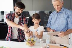 El muchacho y su padre acaban la ensalada para la acción de gracias El viejo hombre se coloca al lado de ellos y mira su tableta  Fotografía de archivo libre de regalías