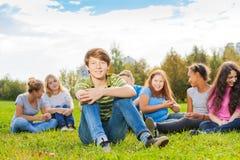 El muchacho y sus amigos se sientan juntos en prado verde Fotos de archivo libres de regalías