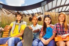 El muchacho y tres muchachas se sientan en banco de madera juntos Foto de archivo libre de regalías