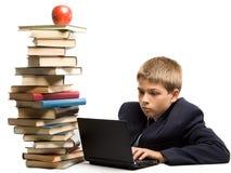 El muchacho y una pila de libros Foto de archivo libre de regalías