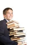 El muchacho y una pila de libros Fotos de archivo libres de regalías