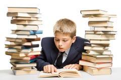 El muchacho y una pila de libros Fotografía de archivo libre de regalías