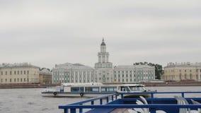 El muelle de Neva del río, St Petersburg Un autobús del río que flota en él, arquitectura hermosa de la ciudad en el fondo metrajes