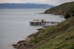El muelle del barco de pesca y proceso vertió penetra hacia fuera de la costa costa rugosa durante la bajamar Fotografía de archivo